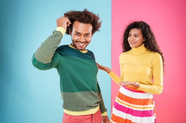 Alegre joven africano confiado de pie delante de su novia confundida sobre fondo azul y rosa