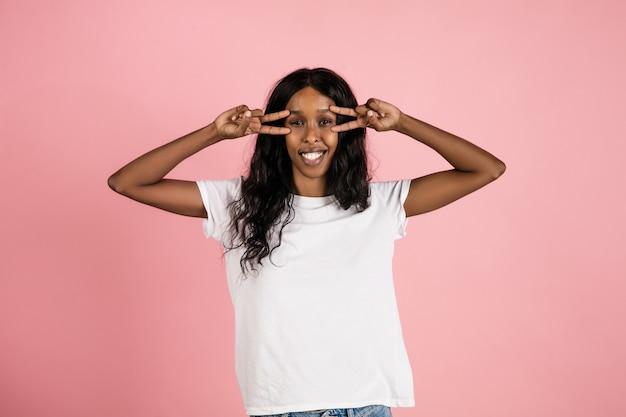 Alegre joven afroamericana aislada en el espacio coralino, emocional y expresivo