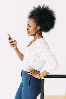 Alegre joven afroamericana mujer de negocios hablando por teléfono celular, de pie cerca de la silla moderna, aislada en blanco