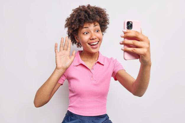 Alegre joven afroamericana de pelo rizado agita la palma en gesto de saludo hace una videollamada a través de una camiseta rosa casual de teléfono inteligente disfruta de una conversación en línea aislada sobre una pared blanca