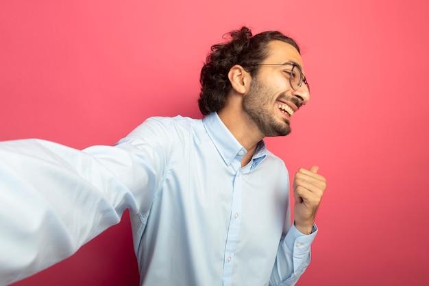 Alegre joven apuesto hombre caucásico con gafas estirando la mano hacia la cámara mirando al lado apuntando detrás aislado sobre fondo carmesí con espacio de copia