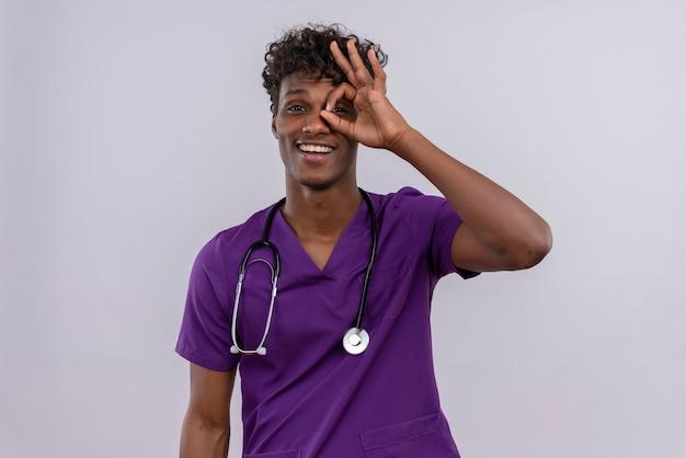 Un alegre joven apuesto médico de piel oscura con cabello rizado vistiendo uniforme violeta con estetoscopio asomándose a través de un agujero formado con el pulgar y el dedo índice