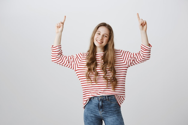 Alegre joven apuntando con el dedo hacia arriba en el anuncio