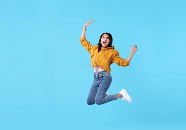 Alegre joven asiática en camisa amarilla saltando y celebrando sobre azul.