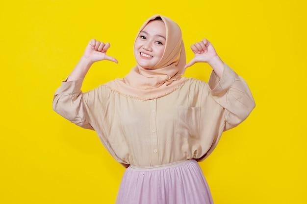Alegre joven asiática con hiyab apunta hacia fuera muestra apuntando con expresión de pulgar, feliz de anunciar el artículo a la venta