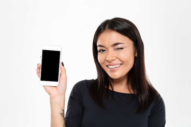 Alegre joven asiática mostrando la pantalla del teléfono móvil