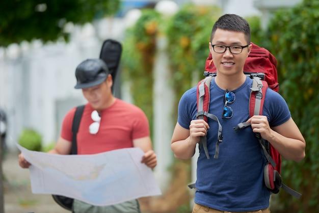 Alegre joven asiática posando con mochila y amigo mirando el mapa