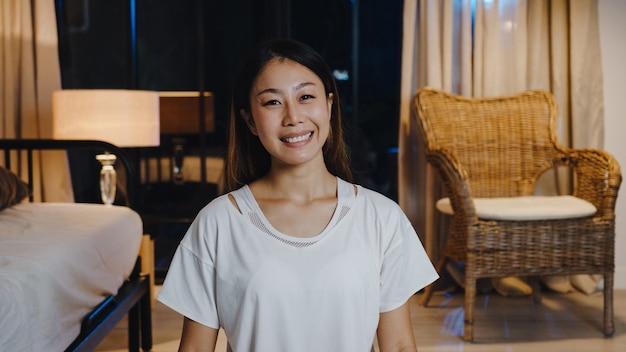 Alegre joven asiática que se siente feliz, sonríe y mira a la cámara usando el teléfono para hacer una videollamada en vivo en la sala de estar en casa por la noche.