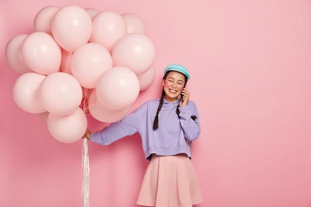 Alegre joven asiática sostiene globos de aire, llama a un amigo a través de un teléfono inteligente, se complace en recibir felicitaciones de personas cercanas, vestidas con ropa de moda.