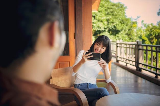 Alegre joven asiática tomando una foto por teléfono inteligente con emoción de felicidad