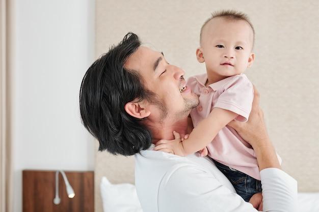 Alegre joven asiático cargando a su pequeño hijo recién nacido y mirándolo con amor y ternura