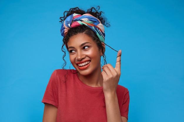 Alegre joven atractiva mujer de cabello oscuro con diadema multicolor sonriendo felizmente y retorciendo su cabello rizado en el dedo, aislado sobre la pared azul