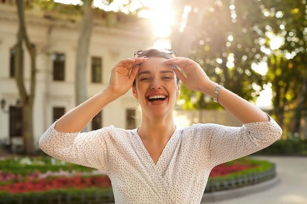 Alegre joven atractiva mujer de cabello oscuro con gafas de sol en la cabeza mientras está de pie sobre la ciudad, riendo felizmente y levantando las manos a la cara