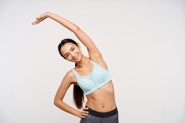 Alegre joven atractiva mujer morena de pelo largo con peinado de cola de caballo haciendo ejercicios de estiramiento y sonriendo felizmente al frente, aislado sobre la pared blanca