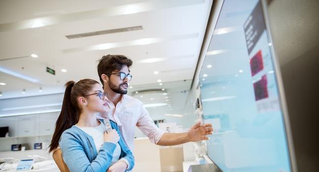 Alegre joven atractiva pareja multirracial mirando televisores de plasma en la tienda de electrónica.