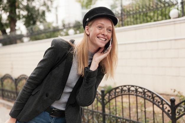 Alegre joven atractiva rubia vestida con elegante ropa de abrigo mientras camina por el jardín de la ciudad, hace una llamada a su amiga y sonríe durante una conversación agradable