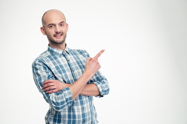 Alegre joven atractivo en camisa a cuadros de pie y apuntando hacia la pared blanca