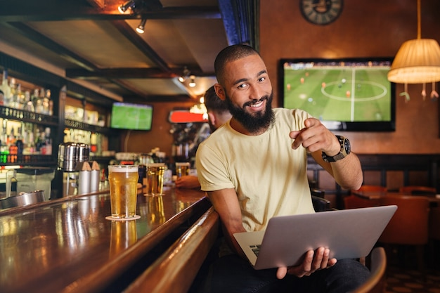 Alegre joven atractivo con portátil sentado en el pub y apuntando a usted