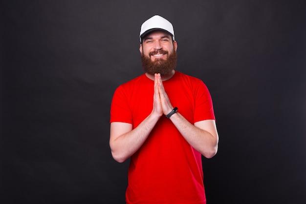 Alegre joven barbudo en camiseta roja rezando y gesticulando