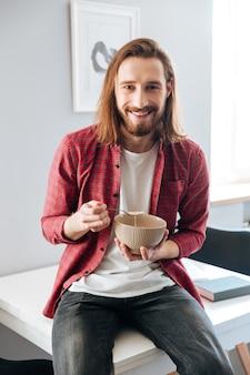 Alegre joven barbudo desayunando en casa