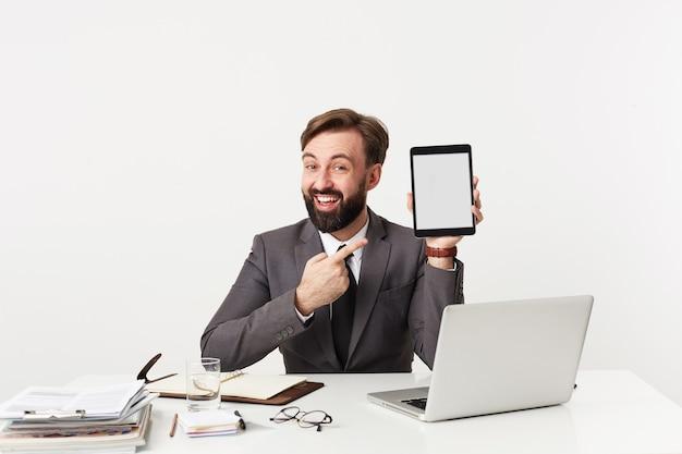 Alegre joven barbudo con peinado de moda apuntando con el dedo índice a la tableta en la mano y sonriendo ampliamente, vestido con traje gris mientras está sentado en la mesa sobre una pared blanca