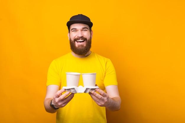 Alegre joven barbudo sostiene dos tazas de bebidas calientes cerca de una pared amarilla sonriendo