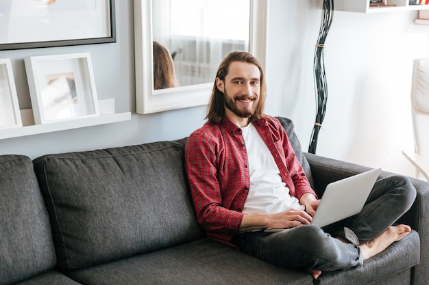 Alegre joven barbudo usando laptop en el sofá en casa