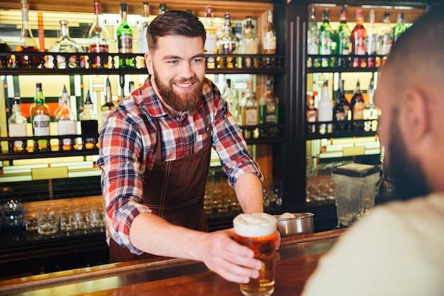 Alegre joven barman barbudo atractivo dando vaso de cerveza al cliente en el bar