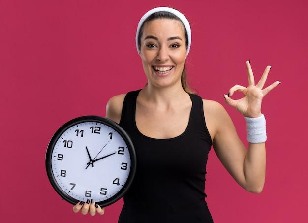 Alegre joven bastante deportivo vistiendo diadema y muñequeras sosteniendo el reloj haciendo el signo de ok