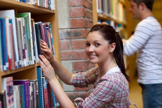 Alegre joven buscando un libro