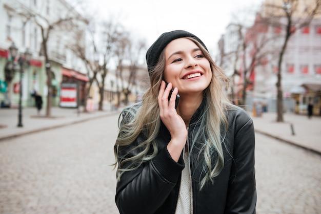Alegre joven caminando en la calle y hablando por teléfono.