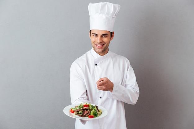 Alegre joven cocinero en uniforme sosteniendo ensalada apuntando a usted.