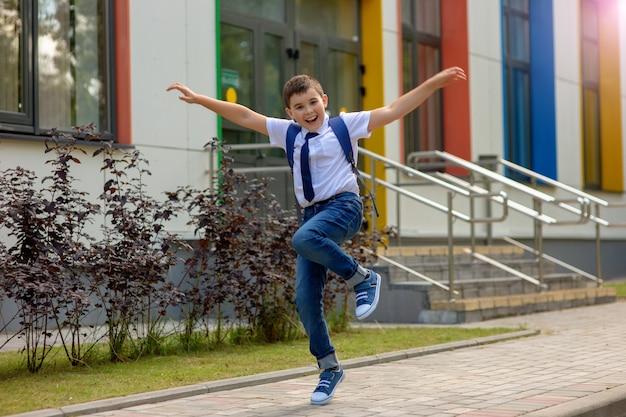 Alegre joven colegial saltando contra la escuela.