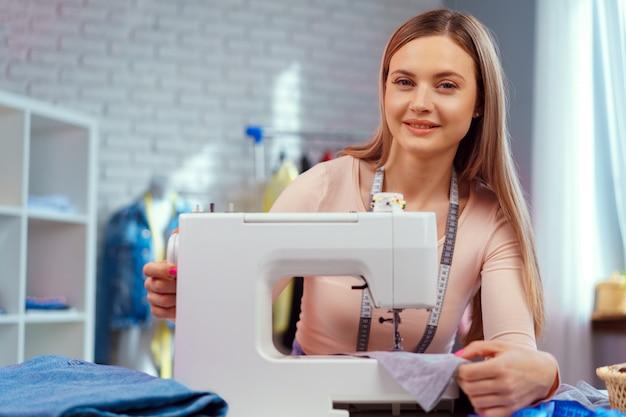 Alegre joven costurera sentada en la mesa de trabajo en su oficina