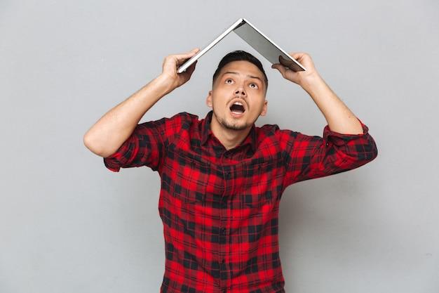 Alegre joven en cuadros escoceses sosteniendo portátil sobre la cabeza
