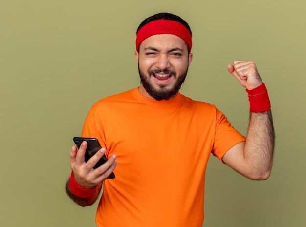 Alegre joven deportivo con diadema y muñequera sosteniendo el teléfono y mostrando sí gesto aislado sobre fondo verde oliva