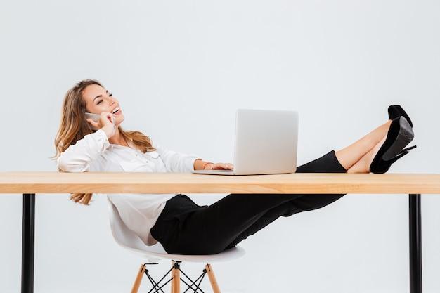 Alegre joven empresaria con portátil y hablando por teléfono celular con las piernas en la mesa sobre fondo blanco.
