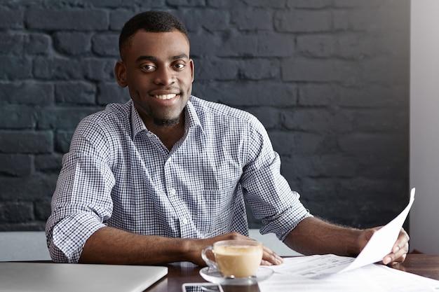 Alegre joven empresario africano exitoso sosteniendo un trozo de papel