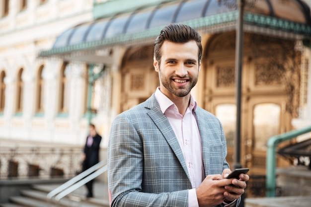 Alegre joven empresario caminando chateando por teléfono