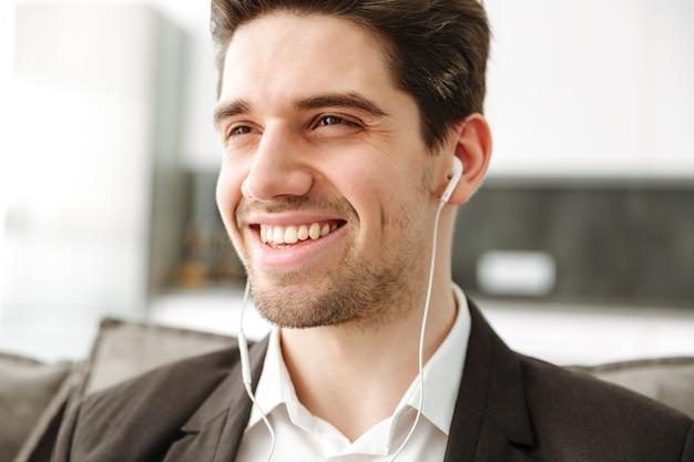 Alegre joven empresario en casa escuchando música