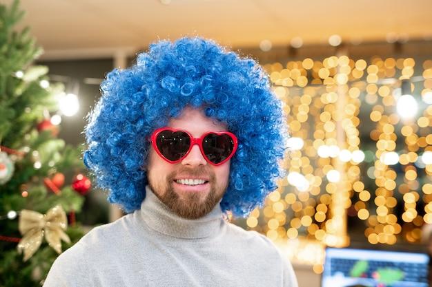 Alegre joven empresario de peluca rizada azul y gafas de sol en forma de corazón de pie el día de navidad en la oficina