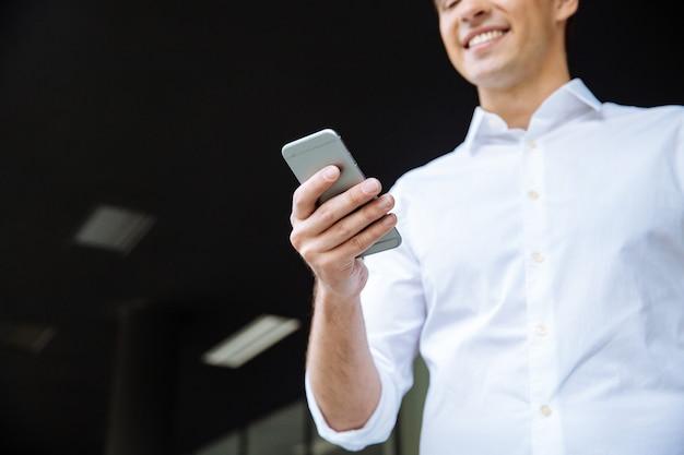 Alegre joven empresario sosteniendo portátil y hablando por teléfono móvil cerca del centro de negocios