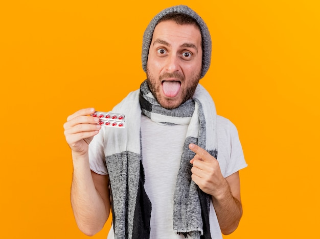 Alegre joven enfermo vistiendo gorro de invierno y bufanda sosteniendo y apunta a las píldoras que muestran la lengua aislada sobre fondo amarillo
