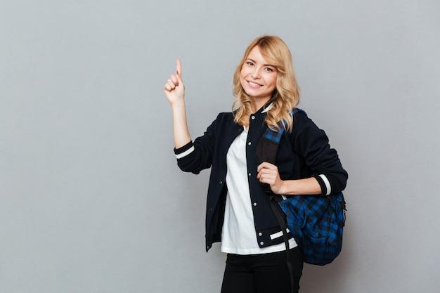 Alegre joven estudiante con mochila señalando