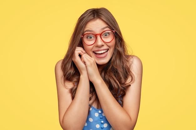 Alegre joven con gafas posando contra la pared amarilla