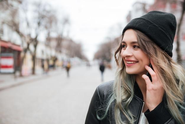 Alegre joven hablando por teléfono móvil.
