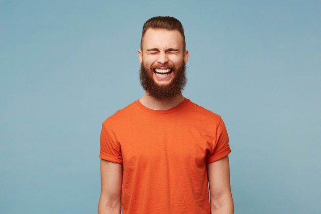 Alegre joven lindo se ríe alegremente mientras escucha una anécdota divertida de un amigo, tiene una barba espesa, posa contra la pared azul del estudio.