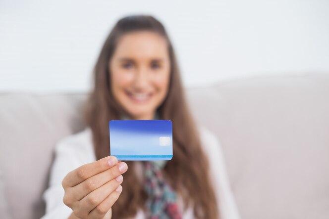 Alegre joven modelo con su tarjeta de crédito