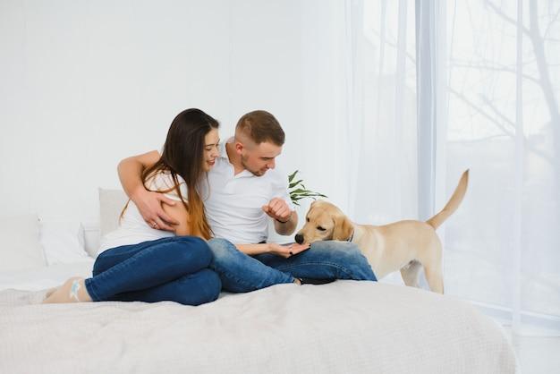 Alegre joven morena juega con su perro favorito en la cama