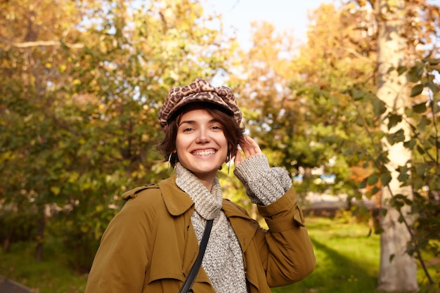 Alegre joven mujer morena de pelo muy corto con trinchera, suéter de punto y sombrero con estampado de leopardo mientras posa sobre el jardín de la ciudad, está de buen humor y sonriendo ampliamente